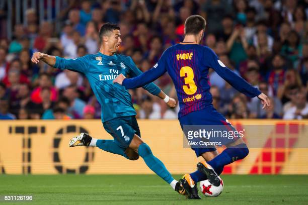 Cristiano Ronaldo of Real Madrid CF shoots the ball under pressure from Gerard Pique of FC Barcelona during the Supercopa de Espana Supercopa Final...