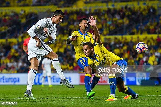 Cristiano Ronaldo of Real Madrid CF shoots towards goal under a challenge by Jonathan Viera and Helder Lopes of UD Las Palmas during the La Liga...