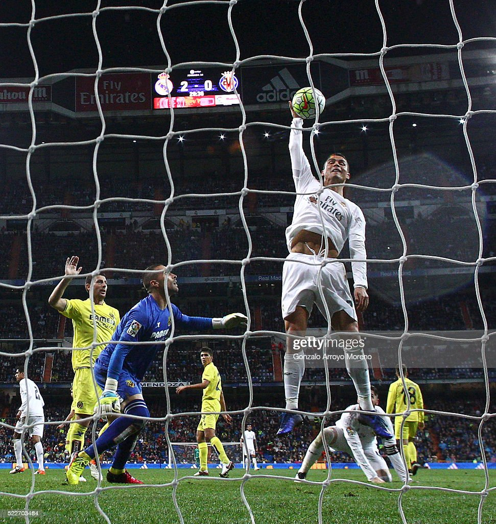 Cristiano Ronaldo (L) of Real Madrid CF touches the ball with the hand after failing to score ahead goalkeeper Sergio Asenjo (R) of Villarreal CF during the La Liga match between Real Madrid CF and Villarreal CF at Estadio Santiago Bernabeu on April 20, 2016 in Madrid, Spain.