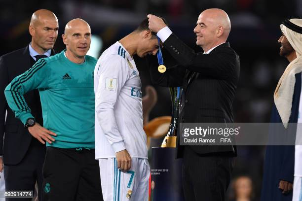 Cristiano Ronaldo of Real Madrid collects his winners medal from Gianni Infantino during the FIFA Club World Cup UAE 2017 Final between Gremio and...