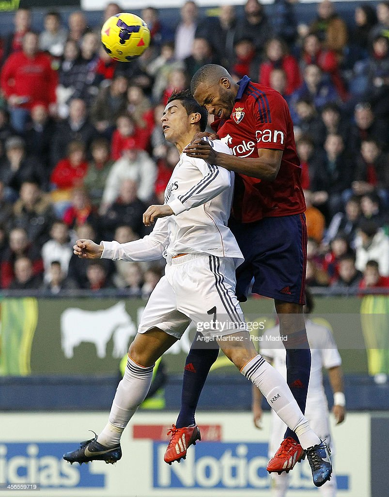 Cristiano Ronaldo of Real Madrid competes for a high ball with Jordan Loties of CA Osasuna during the La Liga match between CA Osasuna and Real Madrid at Estadio Reyno de Navarra on December 14, 2013 in Pamplona, Spain.