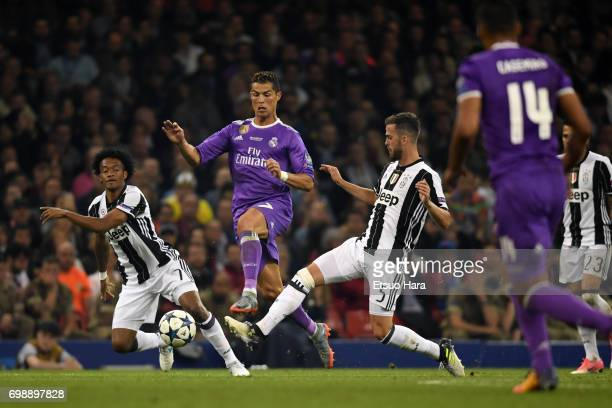 Cristiano Ronaldo of Real Madrid competes for the ball against Miralem Pjanic and Juan Cuadrado of Juventus during the UEFA Champions League final...