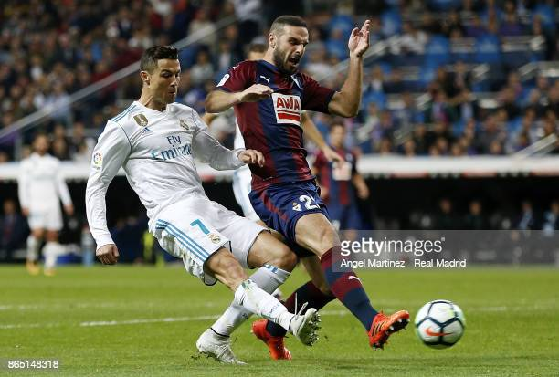 Cristiano Ronaldo of Real Madrid competes for the ball with David Lomban of Eibar during the La Liga match between Real Madrid and Eibar at Estadio...