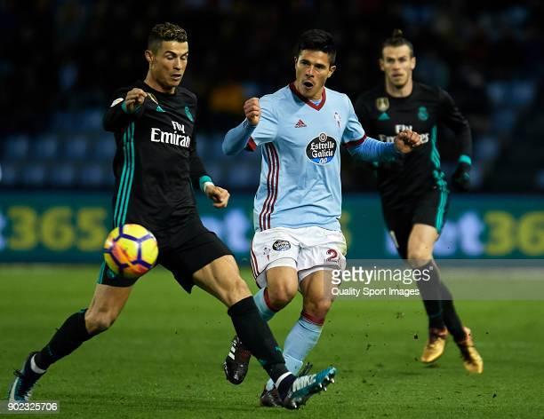 Cristiano Ronaldo of Real Madrid competes for the ball with Facundo Roncaglia of Celta de Vigo during the La Liga match between Celta de Vigo and...