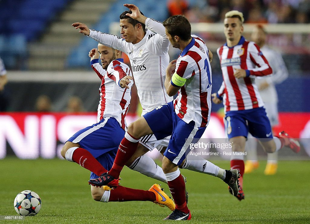 Cristiano Ronaldo of Real Madrid competes for the ball with Gabi (R) and Mario Suarez of Atletico de Madrid during the UEFA Champions League Quarter Final first leg match between Club Atletico de Madrid and Real Madrid CF at Vicente Calderon Stadium on April 14, 2015 in Madrid, Spain.