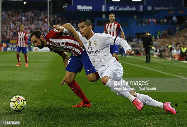 Cristiano Ronaldo of Real Madrid competes for the ball with Juanfran Torres of Atletico de Madrid during the La Liga match between Club Atletico de...