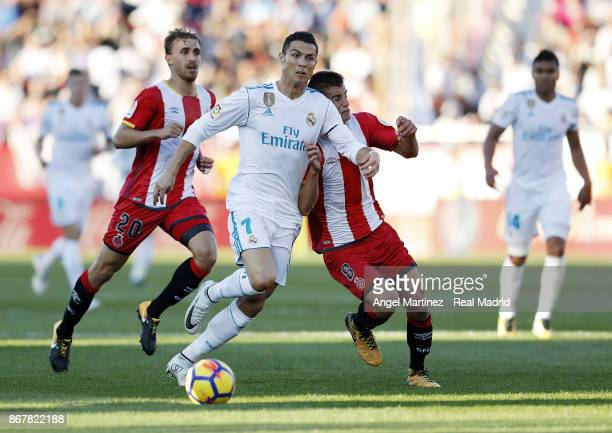 Cristiano Ronaldo of Real Madrid competes for the ball with Pere Pons of Girona during the La Liga match between Girona and Real Madrid at Estadi de...