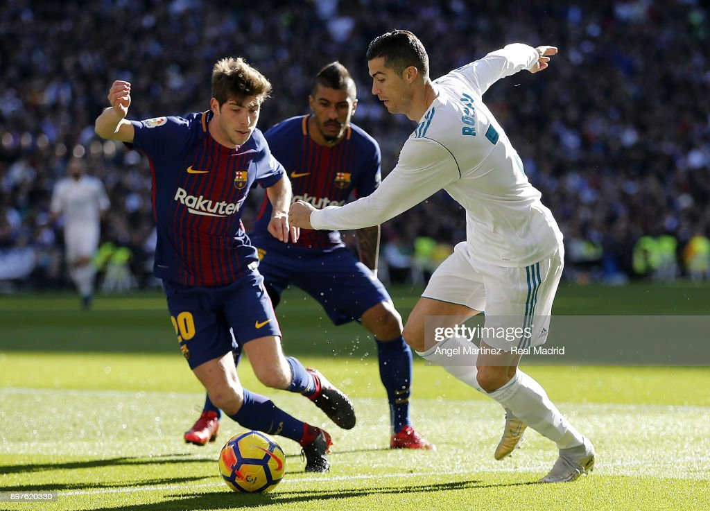 Cristiano Ronaldo of Real Madrid competes for the ball with Sergi Roberto of FC Barcelona during the La Liga match between Real Madrid and Barcelona at Estadio Santiago Bernabeu on December 23, 2017 in Madrid, Spain.