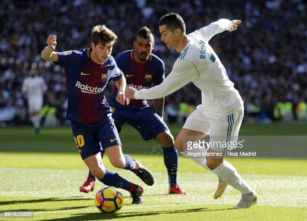 Cristiano Ronaldo of Real Madrid competes for the ball with Sergi Roberto of FC Barcelona during the La Liga match between Real Madrid and Barcelona...