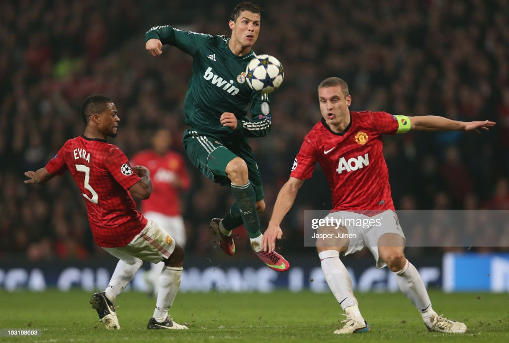 Cristiano Ronaldo of Real Madrid competes with Nemanja Vidic and Patrice Evra of Manchester United during the UEFA Champions League Round of 16 Second leg match between Manchester United and Real Madrid at Old Trafford on March 5, 2013 in Manchester, United Kingdom.