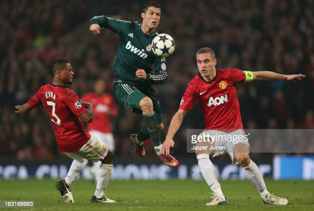 Cristiano Ronaldo of Real Madrid competes with Nemanja Vidic and Patrice Evra of Manchester United during the UEFA Champions League Round of 16...