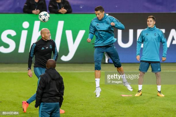 Cristiano Ronaldo of Real Madrid controls the ball Head coach Zinedine Zidane of Real Madrid looks on during a Real Madrid training session ahead of...