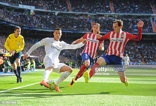 Cristiano Ronaldo of Real Madrid crosses the ball while being challenged by Diego Godin and Felipe Luis of Club Atletico de Madridduring the La Liga...