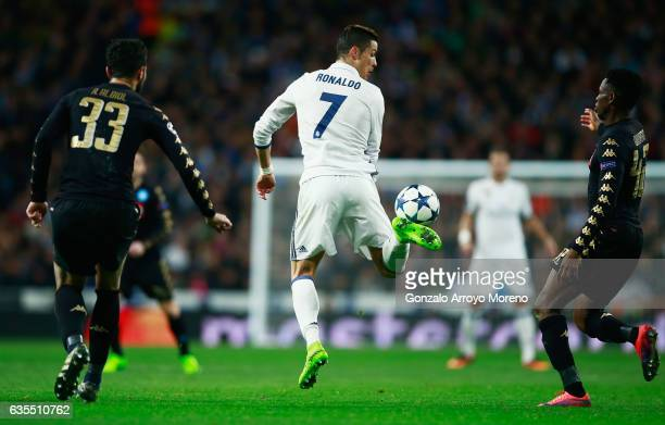 Cristiano Ronaldo of Real Madrid flicks the ball as Raul Albiol and Amadou Diawara of Napoli look on during the UEFA Champions League Round of 16...