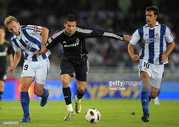 Cristiano Ronaldo of Real Madrid gets between Imanol Agirretxe and Diego Rivas of Real Sociedad during the La Liga match between Real Sociedad and...