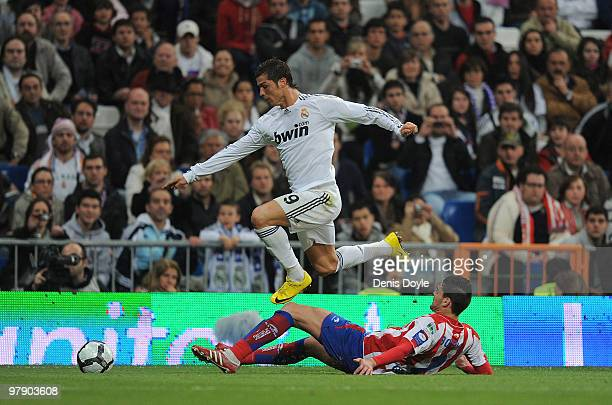 Cristiano Ronaldo of Real Madrid gets past Botia of Sporting Gijon during the La Liga match between Real Madrid and Sporting Gijon at Estadio...