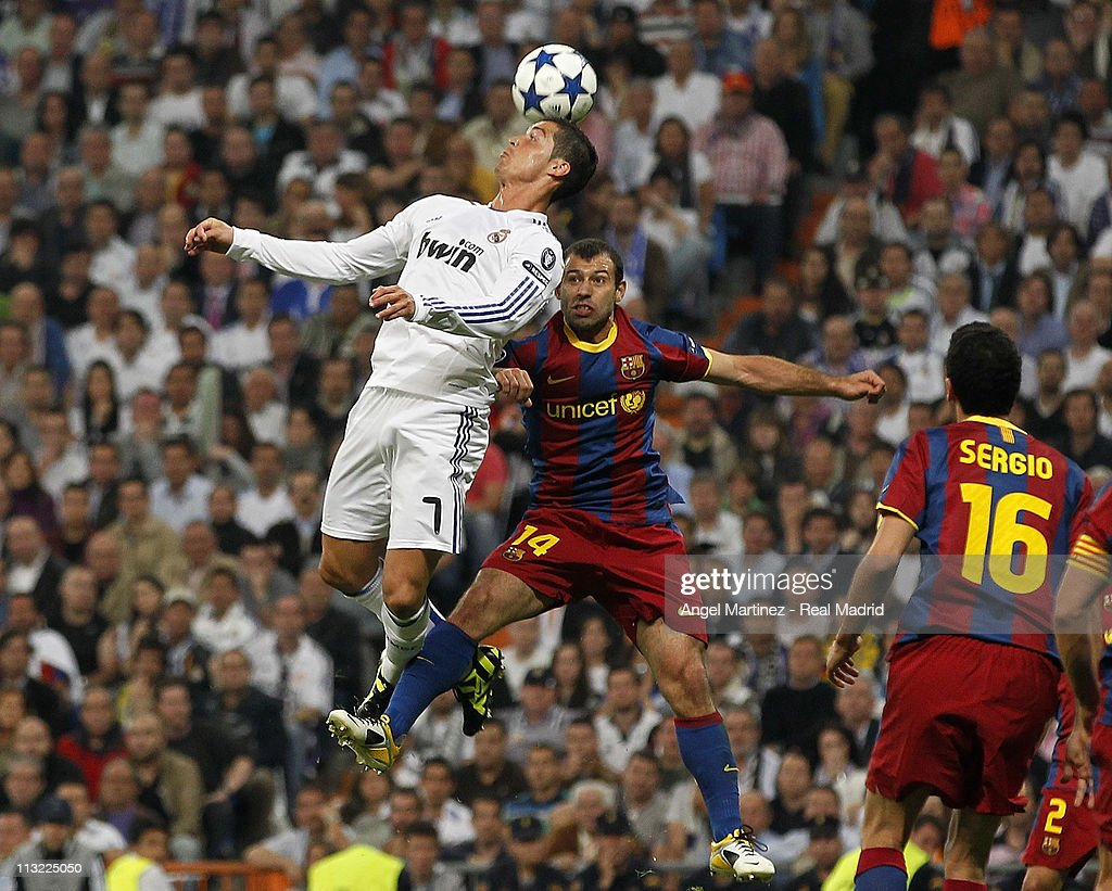 Cristiano Ronaldo of Real Madrid heads the ball against Javier Mascherano during the UEFA Champions League Semi Final first leg match between Real Madrid and Barcelona at Estadio Santiago Bernabeu on April 27, 2011 in Madrid, Spain.