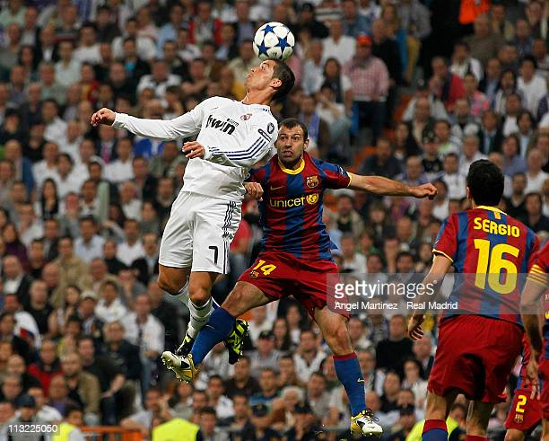 Cristiano Ronaldo of Real Madrid heads the ball against Javier Mascherano during the UEFA Champions League Semi Final first leg match between Real...