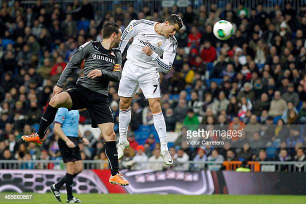 Cristiano Ronaldo of Real Madrid heads the ball beside Sergio Garcia of Espanyol during the Copa del Rey Quarter Final second leg match between Real...