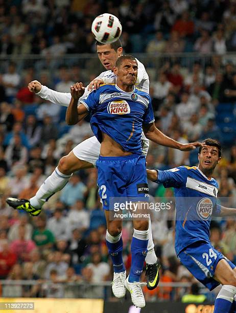 Cristiano Ronaldo of Real Madrid heads the ball to score his side opening goal against Cata Diaz of Getafe during the La Liga match between Real...