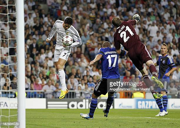 Cristiano Ronaldo of Real Madrid heads the ball to score the opening goal past goalkeeper Johan Wiland and Ragnar Sigurdsson of FC Copenhagen during...