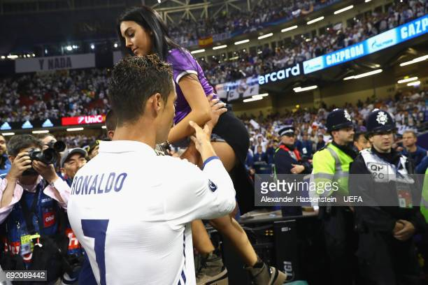 Cristiano Ronaldo of Real Madrid helps his girlfriend Georgina Rodriguez to enter the pitch after the UEFA Champions League Final between Juventus...