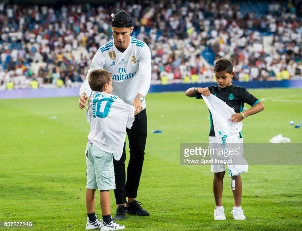 MADRID SPAIN AUGUST 16 Cristiano Ronaldo of Real Madrid helps his son's friend putting a jersey on after their Supercopa de Espana Final 2nd Leg...