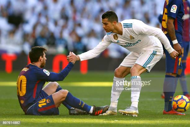 Cristiano Ronaldo of Real Madrid helps Lionel Messi of Barcelona during the La Liga match between Real Madrid and Barcelona at Estadio Santiago...