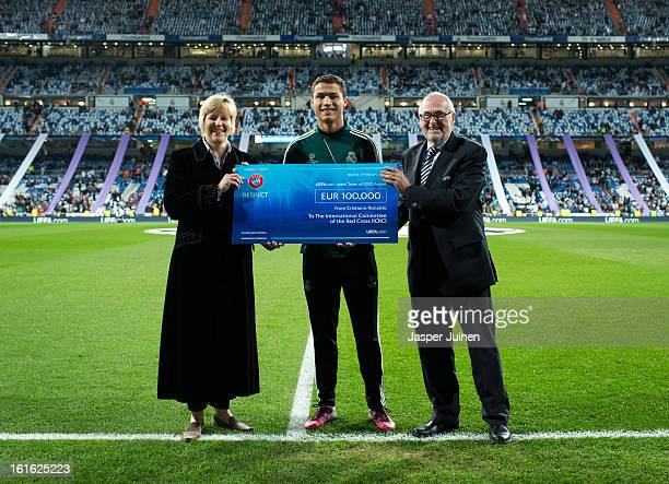 Cristiano Ronaldo of Real Madrid holds a 100000 Euro UEFA charity cheque standing in between Peter Gillieron member of the UEFA Executive Committee...