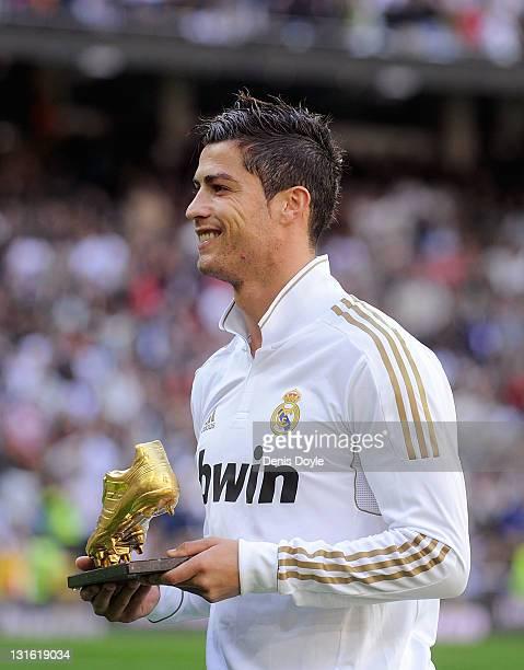 Cristiano Ronaldo of Real Madrid holds his Golden Boot 2011 award before the La Liga match between Real Madrid and Osasuna at Estadio Santiago...