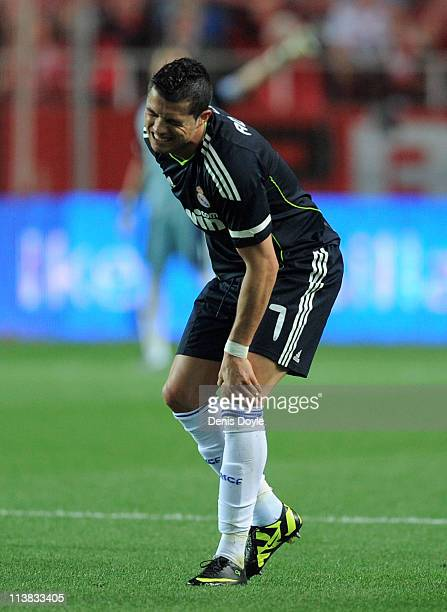Cristiano Ronaldo of Real Madrid holds his knee after taking a knock during the La Liga match between Sevilla and Real Madrid at Estadio Ramon...