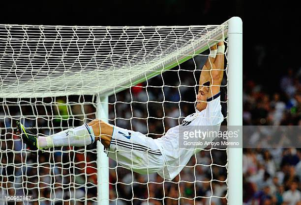 Cristiano Ronaldo of Real Madrid holds onto the Barcelona goal during the Supercopa second leg match between Real Madrid and Barcelona at Estadio...