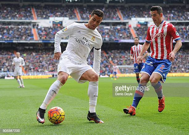 Cristiano Ronaldo of Real Madrid in action against Luis Hernandez of Sporting Gijon during the La Liga match between Real Madrid CF and Sporting...