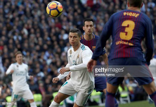 Cristiano Ronaldo of Real Madrid in action against Sergio Busquets and Gerard Pique of Barcelona during the La Liga match between Real Madrid and...