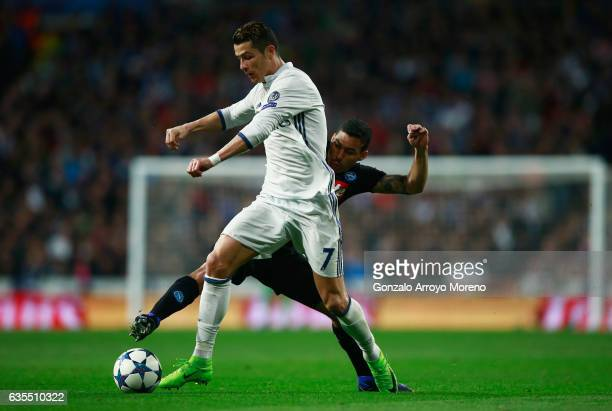 Cristiano Ronaldo of Real Madrid is challenged by Allan of Napoli during the UEFA Champions League Round of 16 first leg match between Real Madrid CF...