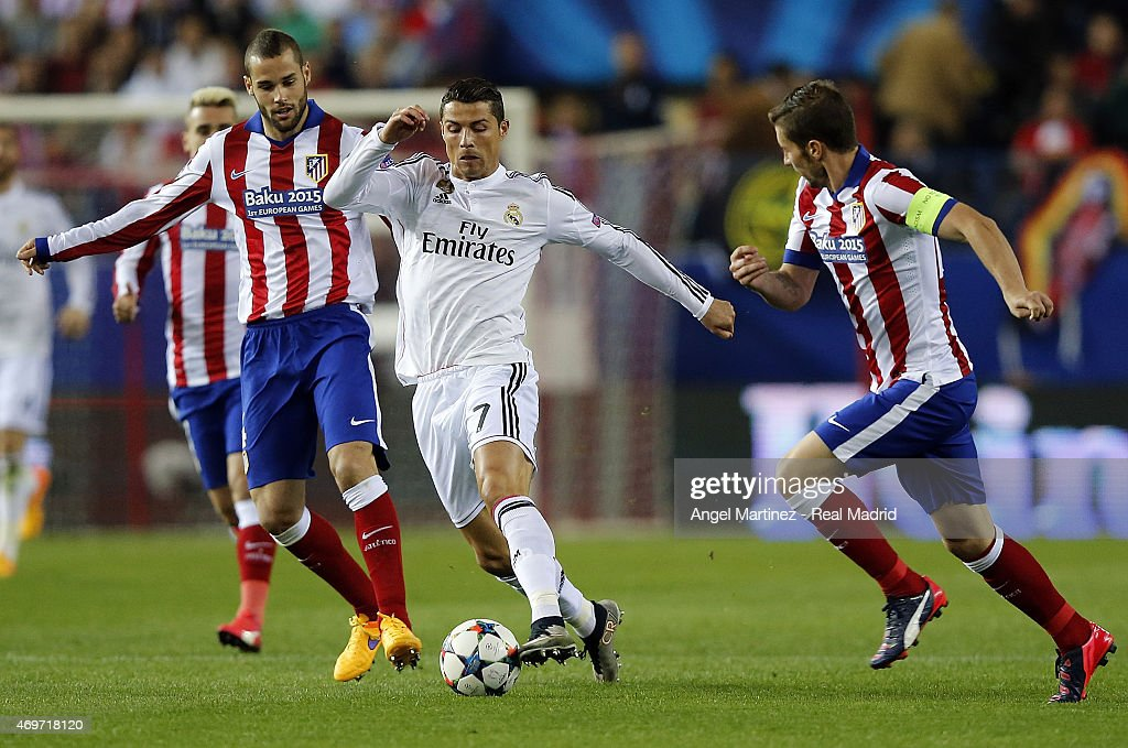 Cristiano Ronaldo of Real Madrid is chased by Gabi (R) and Mario Suarez of Atletico de Madrid during the UEFA Champions League Quarter Final first leg match between Club Atletico de Madrid and Real Madrid CF at Vicente Calderon Stadium on April 14, 2015 in Madrid, Spain.