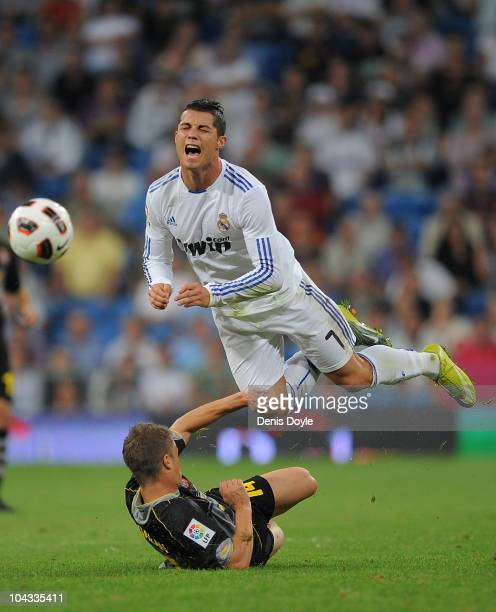 Cristiano Ronaldo of Real Madrid is fouled by Ernesto Galan of Espanyol during the La Liga match between Real Madrid and Espanyol at Estadio Santiago...