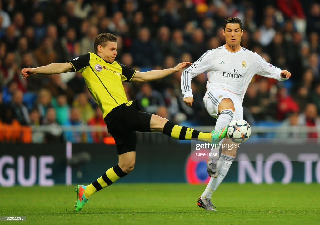 Cristiano Ronaldo of Real Madrid is tackled by Lukasz Piszczek of Borussia Dortmund during the UEFA Champions League Quarter Final first leg match between Real Madrid and Borussia Dortmund at Estadio Santiago Bernabeu on April 2, 2014 in Madrid, Spain.