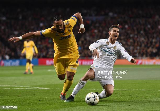 Cristiano Ronaldo of Real Madrid is tackled by Medhi Benatia of Juventus during the UEFA Champions League Quarter Final Second Leg match between Real...