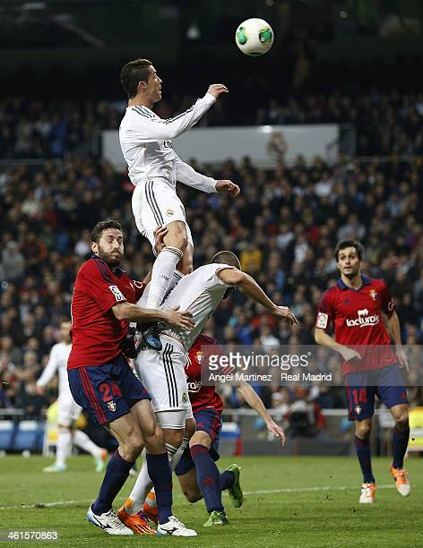 Cristiano Ronaldo of Real Madrid jumps for the ball over Karim Benzema and Damia Abella of Osasuna during the Copa del Rey round of 16 first leg...