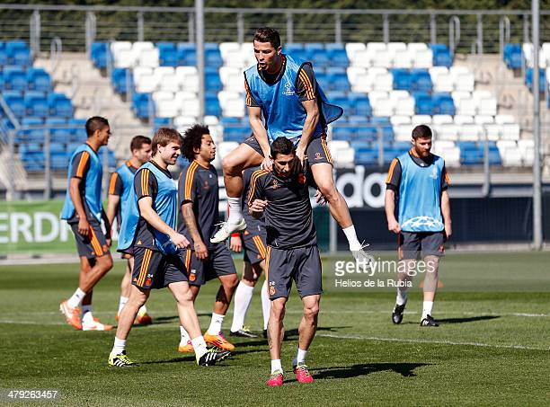 Cristiano Ronaldo of Real Madrid jumps over his teammate's shoulders Angel Di Maria during a training session ahead of their UEFA Champions League...