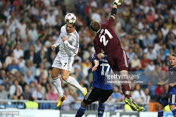 Cristiano Ronaldo of Real Madrid jumps to head the ball and to score his sides opening goal under pressure from Johan Wiland of FC Copenhagen during...