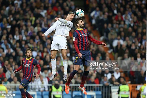 Cristiano Ronaldo of Real Madrid jumps to win a header with Gerard Pique of FC Barcelona during the La Liga football match between Real Madrid and FC...