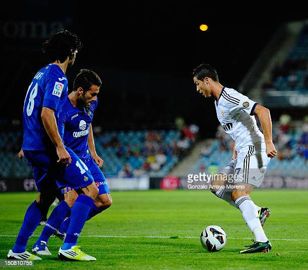 Cristiano Ronaldo of Real Madrid leads the ball while Angel Lafita and Xavi Torres of Getafe looks on during the la Liga match between Getafe and...