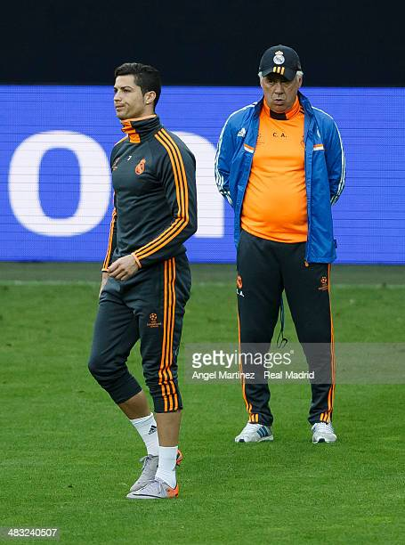 Cristiano Ronaldo of Real Madrid leaves the pitch beside head coach Carlo Ancelotti during a training session ahead of their UEFA Champions League...