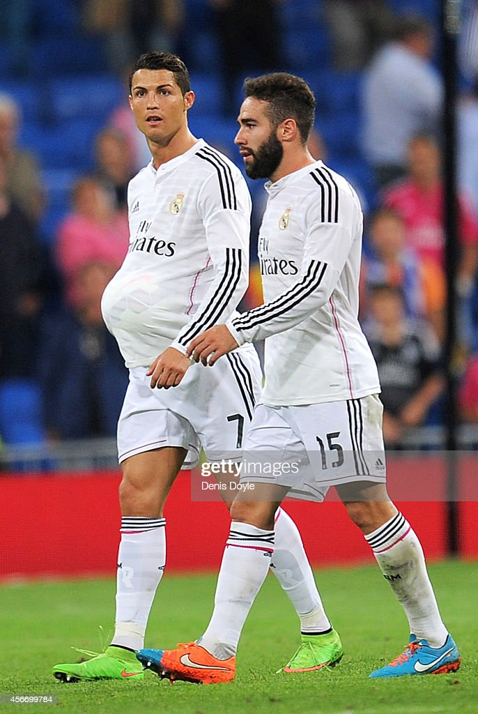 Cristiano Ronaldo of Real Madrid leaves the pitch with the ball under his shirt beside Daniel Carvajal after scoring a hat trick in his team's 5-0 victory over Athletic Club during the La Liga match between Real Madrid CF and Athletic Club at Estadio Santiago Bernabeu on October 5, 2014 in Madrid, Spain.