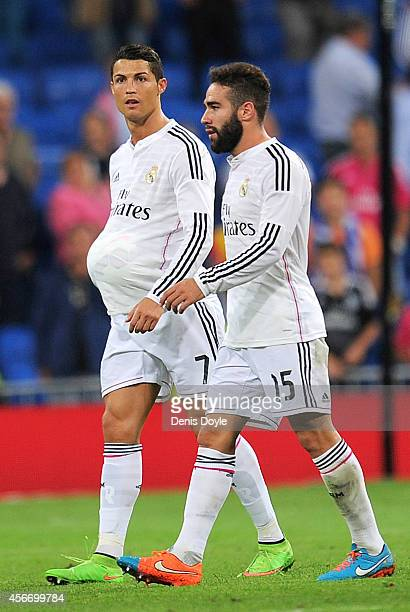 Cristiano Ronaldo of Real Madrid leaves the pitch with the ball under his shirt beside Daniel Carvajal after scoring a hat trick in his team's 50...