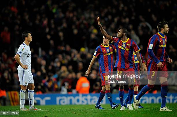 Cristiano Ronaldo of Real Madrid looks on as Eric Abidal of Barcelona gestures after Barcelona scored five goals againts Real Madrid during the La...