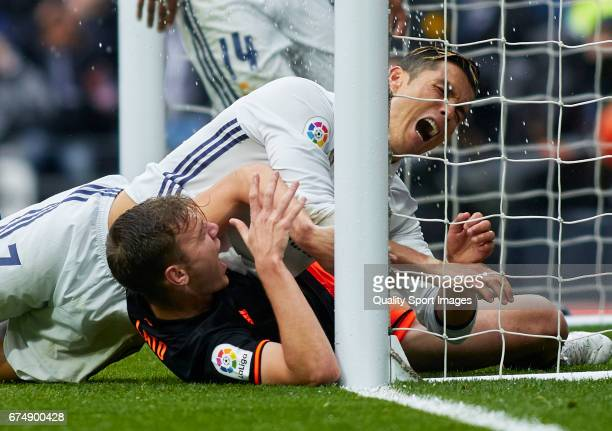 Cristiano Ronaldo of Real Madrid reacts after crashing against the goalposts with Lato of Valencia during the La Liga match between Real Madrid CF...