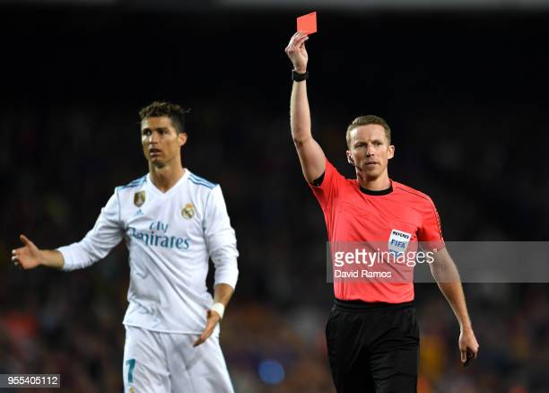 Cristiano Ronaldo of Real Madrid reacts as Alejandro Jose Hernandez Hernandez shows a red card to Sergi Roberto of Barcelona as he is sent off during...